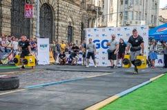 利沃夫州,乌克兰- 2017年8月:一位坚强的爱好健美者运动员举一个巨大的钢重的管子到在enthusia前面的大力士比赛 免版税库存照片