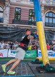 利沃夫州,乌克兰- 2017年8月:一位坚强的爱好健美者运动员举一个巨大的钢重的管子到在enthusia前面的大力士比赛 图库摄影