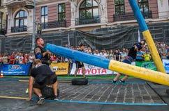 利沃夫州,乌克兰- 2017年8月:一位坚强的爱好健美者运动员举一个巨大的钢重的管子到在enthusia前面的大力士比赛 库存照片