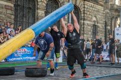 利沃夫州,乌克兰- 2017年8月:一位坚强的爱好健美者运动员举一个巨大的钢重的管子到在enthusia前面的大力士比赛 免版税库存图片