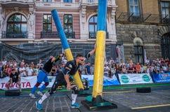 利沃夫州,乌克兰- 2017年8月:一位坚强的爱好健美者运动员举一个巨大的钢重的管子到在enthusia前面的大力士比赛 免版税图库摄影