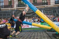 利沃夫州,乌克兰- 2017年8月:一位坚强的爱好健美者运动员举一个巨大的钢重的管子到在enthusia前面的大力士比赛 库存图片