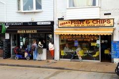 利特尔汉普顿,英国- 2016年10月25日:传统炸鱼加炸土豆片在海滨人行道购物,卖两个吃和外带的鱼和 免版税库存图片