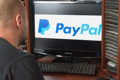 别尔哥罗德州,俄罗斯- 2017年12月11日:人使用PayPal网站 坐在计算机的一名白人 在以前显示器 图库摄影