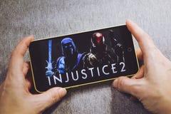 别尔江斯克,乌克兰- 2019年3月4日:拿着有不公道2比赛的手一个智能手机在显示屏上 免版税库存图片