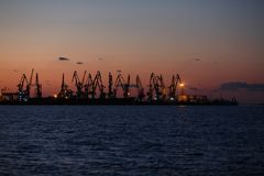 别尔江斯克-乌克兰, 2016年9月02日:许多在海港的大起重机剪影 免版税图库摄影
