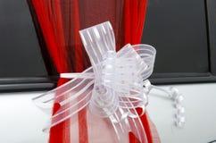 别是巴,以色列 丝带3月24日,与白色透明硬沙的猩红色在一辆白色婚礼汽车鞠躬 免版税库存照片