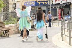 别是巴,以色列 女孩3月24日,蝴蝶狂欢节服装的在街道上的在普珥节 免版税库存图片