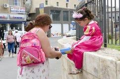 别是巴,以色列 妈妈3月24日,穿上鞋子一件狂欢节礼服的一个女孩在普珥节的街道上 免版税图库摄影