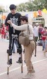 别是巴,以色列 母亲3月24日,在高跷帮助她的儿子走 purim 免版税库存图片