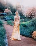 别致的黄色昂贵的豪华礼服的神奇夫人在壮观的庭院里,有长的金发的神奇公主 库存图片
