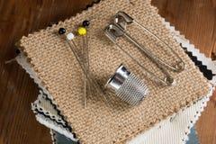 别针和顶针在堆织品样片 库存图片