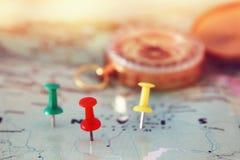 别针附有地图,显示地点或旅行目的地和老指南针 免版税图库摄影