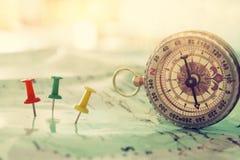 别针附有地图,显示地点或旅行目的地和老指南针 库存图片
