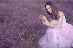 别致的妇女画象有诱惑的组成和坐在紫罗兰色花的领域的长的头发 免版税图库摄影