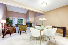 别致的饭厅以与白色椅子的现代玻璃桌为特色 免版税库存图片