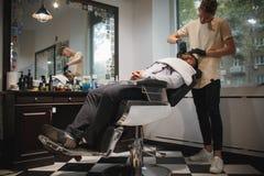 刮一个人的一位英俊的理发师在理发店,得到刮与在被弄脏的轻的背景的一把剃刀 库存照片