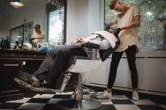 刮一个人的一位英俊的理发师在理发店,得到刮与在被弄脏的轻的背景的一把剃刀 免版税图库摄影