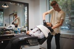 刮一个人的一位英俊的理发师在理发店,得到刮与在被弄脏的轻的背景的一把剃刀 免版税库存照片