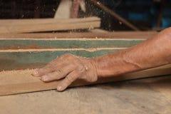 刮一块木头在路由器桌上的工作者的手在木匠业车间 库存照片
