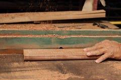 刮一块木头在路由器桌上的资深木匠的手在木匠业车间 免版税库存图片