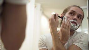刮与剃刀的人胡子在卫生间里 股票录像