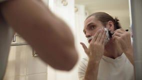 刮与剃刀的人胡子在卫生间里 影视素材
