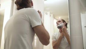 刮与剃刀的人胡子在卫生间里 股票视频