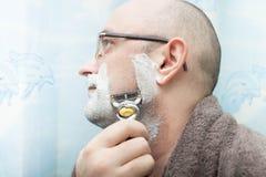 刮他的胡子的严肃的人由剃须刀 免版税库存图片