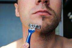 刮他的胡子的严肃的人 免版税库存图片