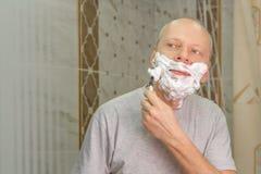 刮他的面孔的一个人的照片 免版税库存照片