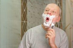 刮他的面孔的一个人的照片 免版税库存图片