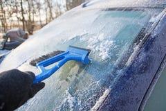从刮冰的汽车和手的冻挡风玻璃与  免版税库存图片