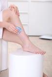 刮她的腿的妇女 免版税库存照片