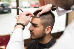 刮有一个普通刀片的美发师人的前额 免版税库存图片