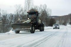 刮板在以后清除在路的雪在汽车前面,在冬天,降雪 免版税库存图片
