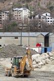 刮板推土机 放置户外站点的砖建筑 房子 免版税图库摄影