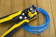刮毛器和导线在木背景 免版税库存照片