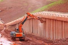 刮混凝土桩的挖掘者 免版税库存照片