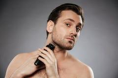 刮胡子的一个严肃的赤裸上身的人的画象 免版税库存照片