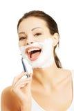 刮胡子的愉快的妇女画象 库存图片
