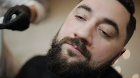 刮胡子的过程在理发店 大师做有葡萄酒普通刀片的理发胡子客户 影视素材
