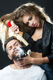 刮英俊的有胡子的人的妇女 库存图片