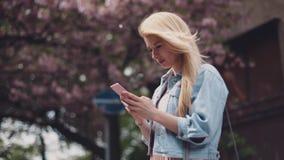 刮风的天气在城市 少妇使用她的手机 在背景的樱花和路标 股票视频