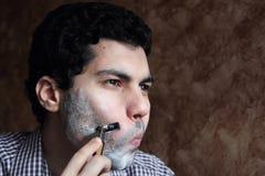 刮他的与剃刀的阿拉伯年轻商人胡子 免版税图库摄影