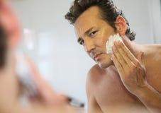 刮他的胡子的一个英俊的人的特写镜头 免版税图库摄影