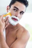 刮他的胡子的英俊的人 免版税库存图片