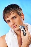 刮年轻人的英俊的人 免版税库存图片