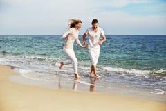 到处乱跑和花费好时间的年轻美好的夫妇在海滩上在度假 儿童有父亲的乐趣一起使用 免版税库存图片