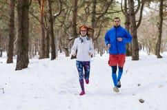 到处乱跑在冬天森林里的愉快的已婚夫妇 免版税图库摄影
